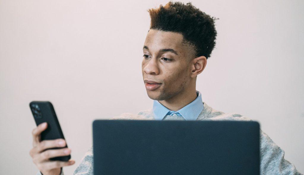 Black man browsing smartphone near laptop